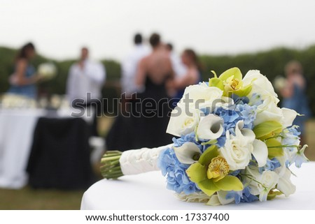 Bridal bouquet with wedding party in background, DOF focus on flowers