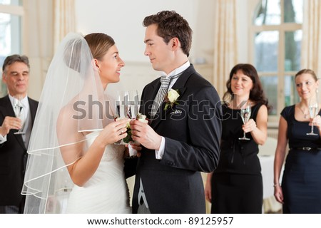 Bridal couple clinking glasses while the guests standing in the background