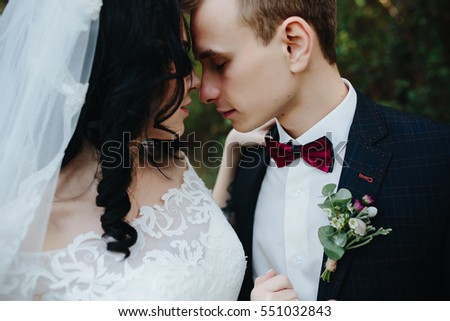 Bridal couple close to each other, posing in park