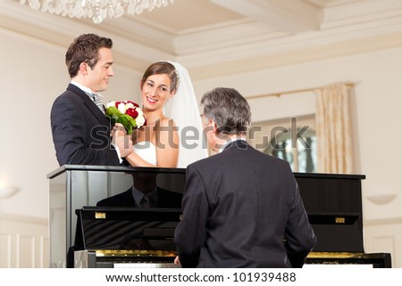 Bridal couple in front of a piano, the pianist is playing a waltz - stock photo