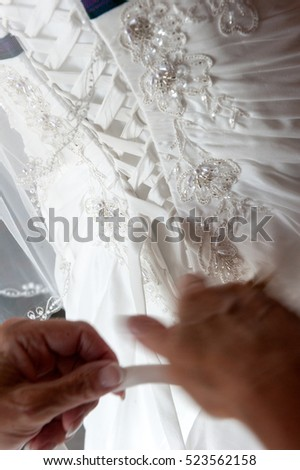 Bridal Dress closeup portrait of a maid of honor helping the bride with her dress
