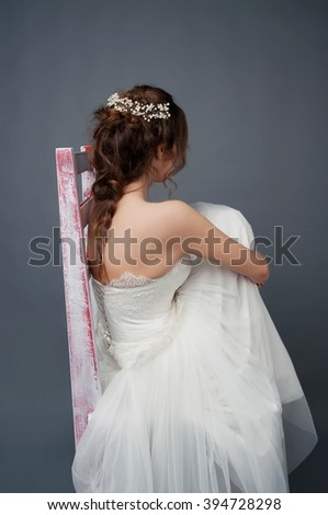 Bridal fashion. Brunette bride with pearl headpiece and white wedding gown view from the back sitting in a pile of tulle fabric. - stock photo