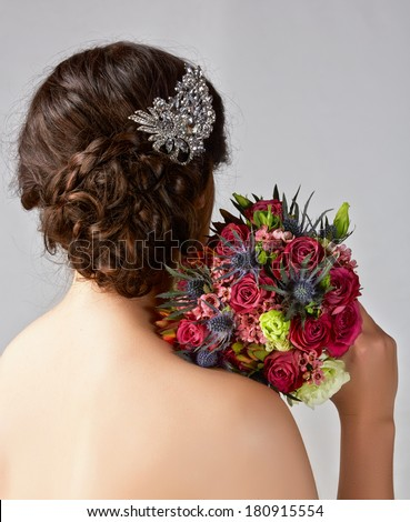 Bridal hairstyle with vintage style hair accessories and red rose bouquet. Brunette Bride. View from the back - stock photo