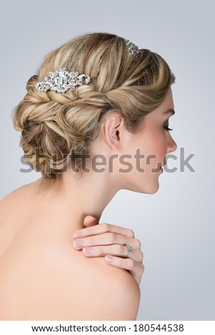 Bridal hairstyle with vintage style hair accessories. Blond Bride. View from the back