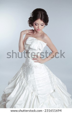 Bridal makeup, hairstyle. Beautiful charming bride in wedding luxurious dress with voluminous skirt, studio photo - stock photo