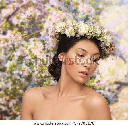bridal, spring and beauty concept - young woman wearing wreath of flowers - stock photo