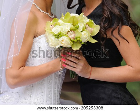 bride and bridesmaid holding wedding bouquet - stock photo