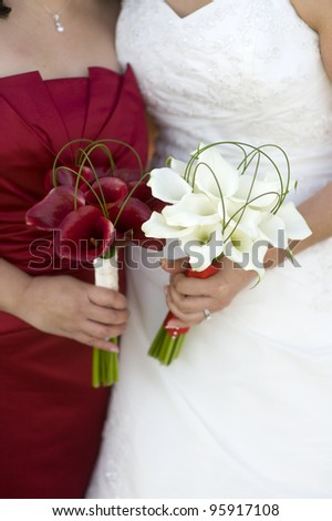 bride and bridesmaid with wedding flowers - stock photo