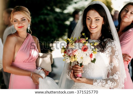 Bride and bridesmaids at  wedding ceremony outdoors - stock photo