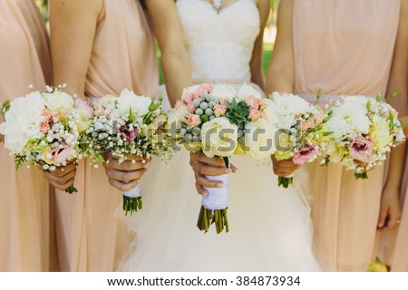 Bride and bridesmaids hand with beautiful flowers - stock photo