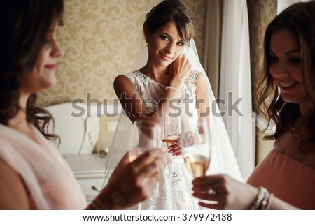 Bride and bridesmaids on the wedding day drinking champagne - stock photo