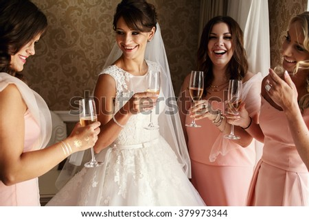 Bride and bridesmaids on the wedding day drinking wine - stock photo