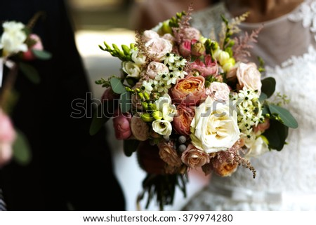 Bride and bridesmaids with bouquet of roses outdoors