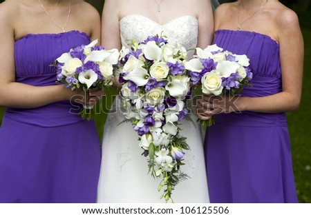 bride and bridesmaids with purple wedding bouquets