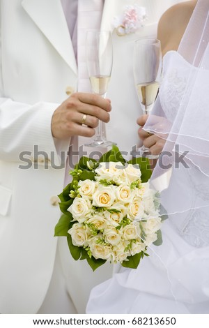 Bride and fiance hold glasses of champagne - stock photo