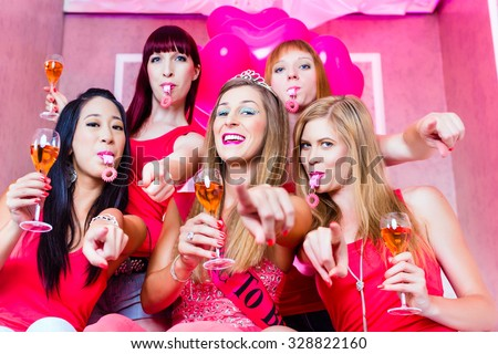 Bride and friends celebrating hen night with champagne and whistles in club  - stock photo