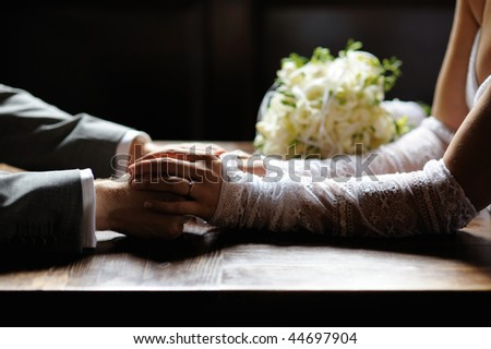 Bride and groom are holding their hands - stock photo