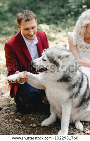 Bride and groom are in the forest with siberian husky.