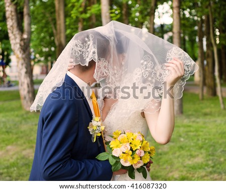 Bride and groom are kissing in the park - stock photo