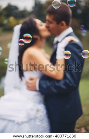 Bride and groom are walking together in a park. They are kissing. Couple is blurred and the soap bubbles are flying in the foreground.  - stock photo