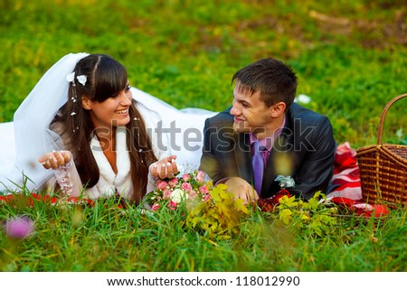 bride and groom at a picnic in autumn are couple on green grass