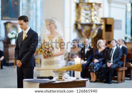 Bride and groom at the church during a wedding ceremony - stock photo