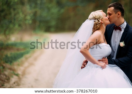Bride and groom at wedding Day hugging Outdoors on spring nature. Bridal couple, Happy Newlywed woman and man embracing in green park. Loving wedding couple outdoor. Bride and groom - stock photo