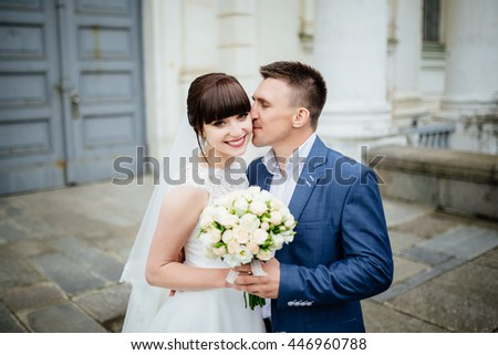 Bride and groom at wedding Day walking Outdoors near architecture. Bridal couple, Newlywed woman and man embracing with love - stock photo