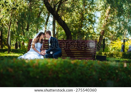 Bride and Groom at wedding Day walking Outdoors on spring nature. Bridal couple, Happy Newlywed woman and man embracing in green park. Loving wedding couple outdoor.