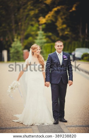Bride and groom at wedding Day walking Outdoors on spring nature. Bridal couple, Happy Newlywed woman and man embracing in green park. Loving wedding couple outdoor. Bride and groom - stock photo