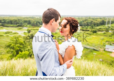 Bride and groom at wedding Day walking Outdoors on spring nature. Happy Newlywed  embracing in green park.
