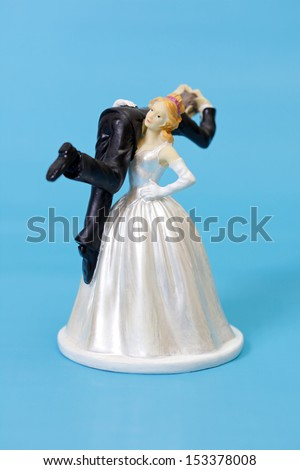 Bride and groom cake topper on blue background - stock photo