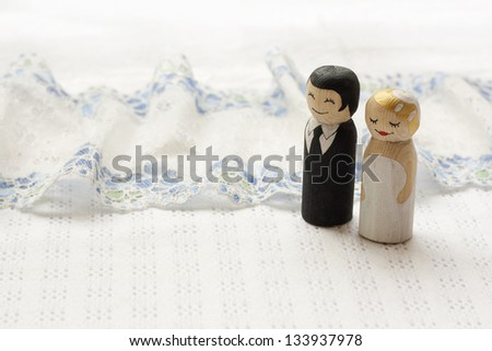 Bride and groom cake topper wooden doodle figures on white fabric background with laces - stock photo