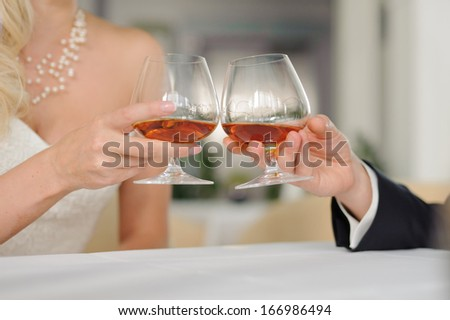 bride and groom clanging glasses with cognac in cafe