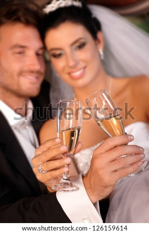 Bride and groom clinking glasses on wedding-day. Focus on champagne flutes. - stock photo