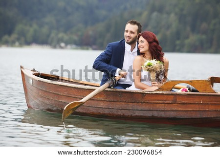 Bride and groom close together in the lake rowing boat  - stock photo