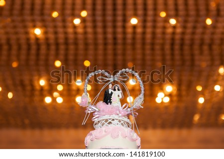 bride and groom couple doll in wedding cake - stock photo