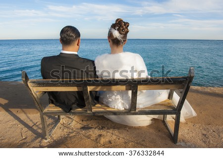 Bride and groom couple sitting on a wooden bench looking out over tropical sea