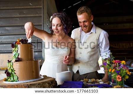 Bride and groom cut their wedding cake at a reception with a tree theme.