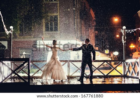Bride and groom dancing in the night under rain - stock photo