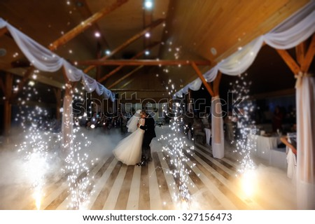 bride and groom dancing on the own wedding with white fume