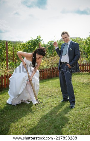 Bride and groom digs the soil on a kitchen garden. Humour. - stock photo