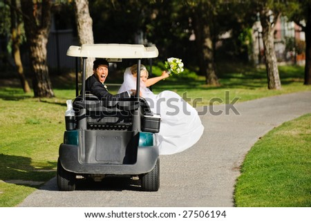 Bride and groom driving a golf cart - stock photo