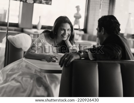 Bride and groom eating at diner - stock photo