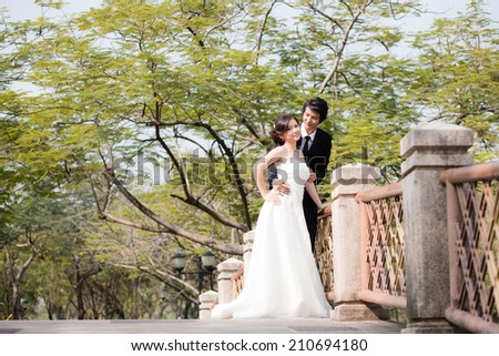 Bride and groom Embrace and looking each other in the garden - stock photo