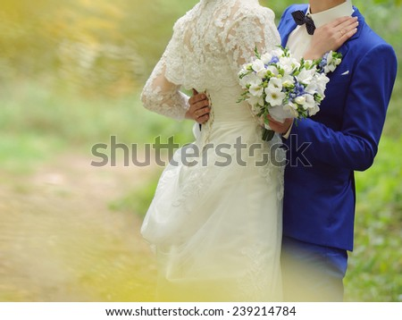 bride and groom embracing in park - stock photo