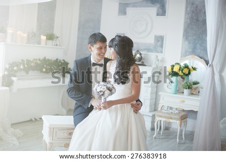 Bride and groom embracing. Newlyweds sitting on the sofa and embracing.