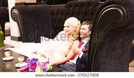 Bride and groom embracing. Newlyweds sitting on the sofa and embracing