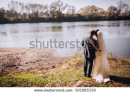 Bride and groom enjoying their love near the autumn river. Reflections from the sun. Sunset. Kissing couple at the nature.