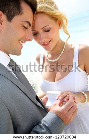 Bride and groom exchanging wedding rings - stock photo